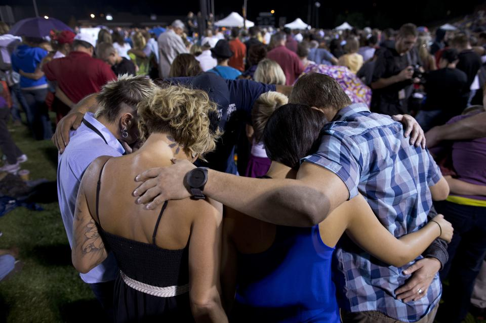 Mourners gather in a circle to pray during a candlelight vigil in Prescott, Ariz. on Tuesday, July 2, 2013 to honor the 19 Granite Mountain Hotshot firefighters who were killed by an out-of-control blaze near Yarnell, Ariz. on Sunday. (AP Photo/Julie Jacobson)