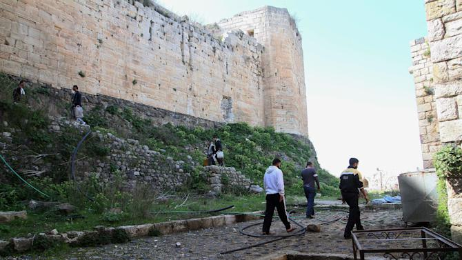 People walk around the Crac des Chevaliers as Syrian troops take reporters on a tour a day after they ousted rebels from the castle located near the village of Hosn, Syria, Friday, March 21, 2014. The Syrian army ousted rebels from the massive Crusader fortress after several hours of fierce fighting, killing at least 93 of them as they fled to neighboring Lebanon, an army commander told reporters on a government-led tour of the area Friday. (AP Photo)