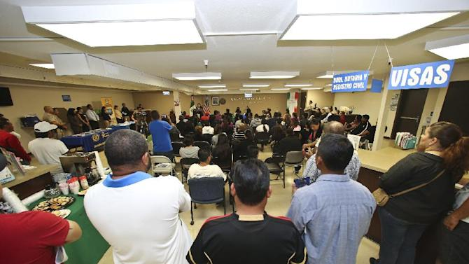 FILE - In this Wednesday, April 23, 2014 file photo, a crowd of approximately 80 immigrants fill a room as they listen to officials explain the process of getting a drivers license, during an information session at the Mexican Consulate, in San Diego. California is gearing up to start issuing driver's licenses to immigrants in the country illegally in a bid to make the roads safer that could also give more than a million people access to state-issued identification. (AP Photo/Lenny Ignelzi,File)