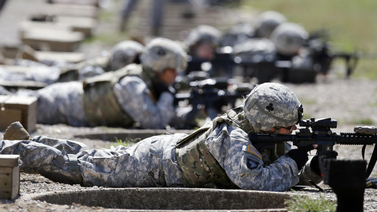 FILE - In this Sept. 18, 2012 file photo, female soldiers from 1st Brigade Combat Team, 101st Airborne Division train on a firing range while testing new body armor in Fort Campbell, Ky., in preparation for their deployment to Afghanistan. The Pentagon is lifting its ban on women serving in combat, opening hundreds of thousands of front-line positions and potentially elite commando jobs after generations of limits on their service, defense officials said Wednesday, Jan. 23, 2013. (AP Photo/Mark Humphrey, File)