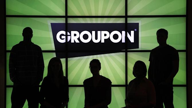 FILE - In this Sept. 22, 2011 file photo, employees at Groupon Inc. pose in silhouette with the company logo in the lobby of the online coupon company's Chicago offices. Groupon will report quarterly financial results after the market closes, Monday May 14, 2012. (AP Photo/Charles Rex Arbogast, File)