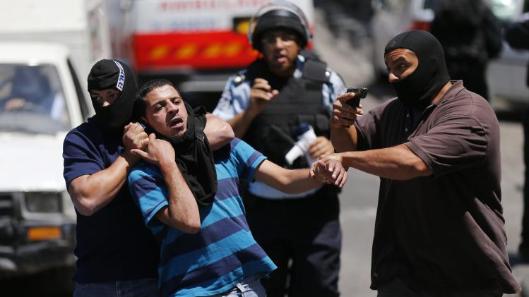 An undercover Israeli police officer holds a gun in the air as another detains a Palestinian suspected of throwing stones in the East Jerusalem neighbourhood of Wadi al-Joz during a protest against the Israeli offensive on Gaza