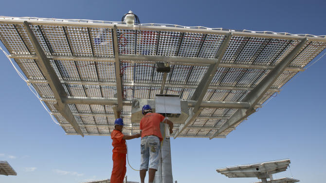 In this photo taken on Monday, Aug. 6, 2012, workers install solar panels at a construction site of a high concentration photovoltaic (HCPV) power plant in Hami city in northwest China's Xinjiang Uygur Autonomous Region. Chinese solar panel makers that grew fast over the past decade are suffering big losses due to slumping global sales and a price war that threaten an industry seen by communist leaders as a role model for hopes to transform China into a technology leader. (AP Photo) CHINA OUT