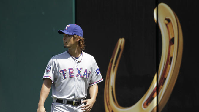 Texas Rangers starting pitcher Yu Darvish walks on the field during warm-ups before a baseball game against the Cleveland Indians in Cleveland on Sunday, May 6, 2012.  (AP Photo/Amy Sancetta)