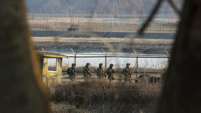 South Korean army soldiers patrol along a barbed-wire fence near the border village of Panmunjom in Paju, South Korea, Wednesday, March 27, 2013. North Korea said Wednesday that it had cut off a key military hotline with South Korea that allows cross border travel to a jointly run industrial complex in the North, a move that ratchets up already high tension and possibly jeopardizes the last major symbol of inter-Korean cooperation.(AP Photo/Ahn Young-joon)