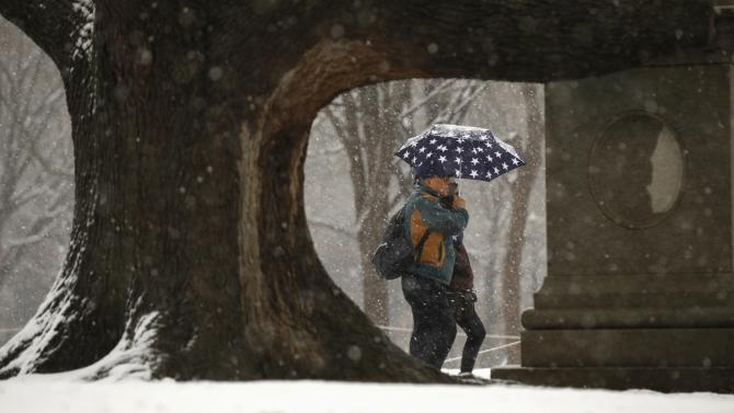 Snow falls as a couple strolls through Lafayette Park near the White House in Washington