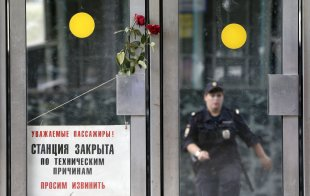 CLICK IMAGE for slideshow: Flowers in memory of victims of Tuesday's accident, in which three carriages derailed on a train during morning rush hour, are left next to a sign informing passengers that the station is closed due to technical reasons, at the entrance to a metro station in Moscow July 16, 2014. Russian state investigators said on Wednesday they had detained two Moscow metro workers suspected of safety breaches that may have caused an accident that killed at least 21 people. REUTERS/Sergei Karpukhin (RUSSIA - Tags: TRANSPORT DISASTER)