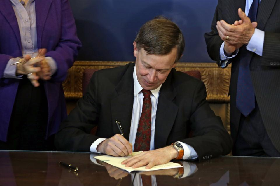 Colorado Gov. John Hickenlooper is applauded by lawmakers as he signs the state's gun control bill into law at the Capitol in Denver on Wednesday, March 20, 2013. (AP Photo/Ed Andrieski, Pool)