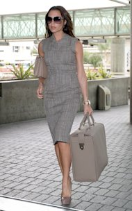 Victoria Beckham travels in style in a gray sheath dress