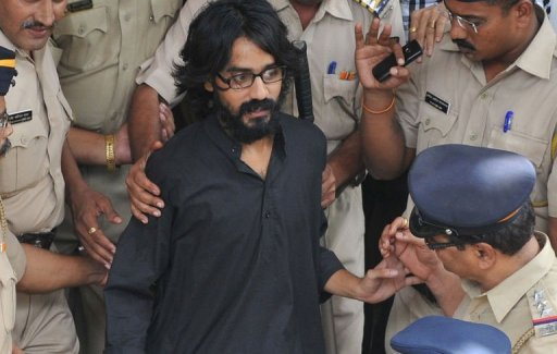 <p>Cartoonist Aseem Trivedi, who has been arrested on sedition charges, is escorted out of the Bandra Metropolitan Magistrate court in Mumbai on September 10, 2012. India's government is facing a mounting domestic and international backlash over the arrest as critics accused it of using colonial era laws to crush dissent.</p>