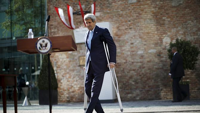 U.S. Secretary of State John Kerry walks using crutches to deliver a statement on the Iran talks in Vienna, Austria