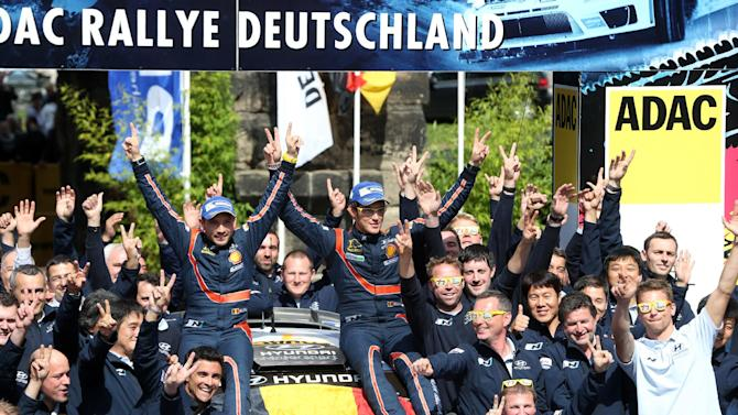 Belgium's Thierry Neuville , center right, and his co-driver Nicolas Gilsoul celebrate with the Hyundai team after winning the Deutschland Rallye, the German WRC stage , in Trier , Germany, Sunday Aug. 24, 2014. Thierry Neuville held his nerve to win the Rally of Germany after Finland's Jari-Matti Latvala and then Britain's Kris Meeke crashed out of the lead on Sunday. (AP Photo/dpa,Thomas Frey)