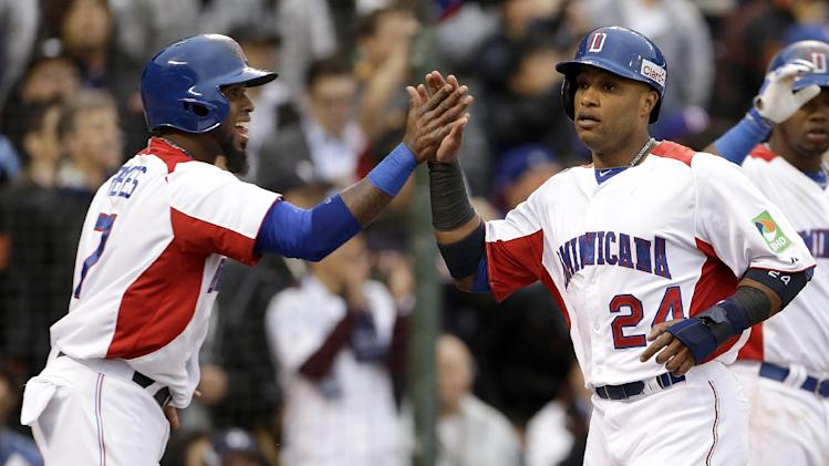 The Dominican Republic's Jose Reyes, left, and Robinson Cano celebrate after scoring against Puerto Rico during the first inning of the championship game of the World Baseball Classic in San Francisco, Tuesday, March 19, 2013. (AP Photo/Eric Risberg)