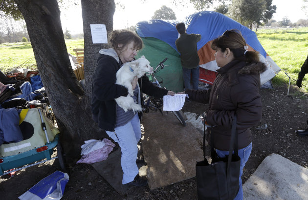 <p>               Wendy Clarke, left, holds her neighbor's dog Hero as she is handed an eviction notice by San Jose city worker Rita Tabaldo as city worker Mark Ruffing, center, attaches a notice to a Clarke's tent at a tent city in San Jose, Calif., Tuesday, March 5, 2013. The Silicon Valley is adding jobs faster than it has in more than a decade as the tech industry roars back. Stocks are soaring and fortunes are once again on the rise. But a more ominous record is also being set this year: food stamp participation just hit a 10 year high, African American wages fell 18 percent in two years and median incomes fell throughout the region. Simply put, while the ultra rich are getting even ultra richer, record numbers of Silicon Valley residents are slipping into poverty. (AP Photo/Jeff Chiu)