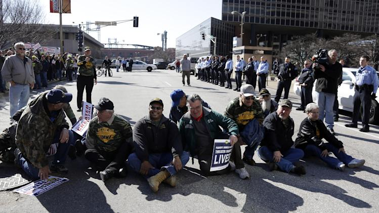 Members of the United Mine Workers of America wait to be arrested by police during protest outside the of headquarters of Peabody Energy, one of the companies the union accuses of orchestrating business deals that bankrupted Patriot Coal, Wednesday, Feb. 13, 2013, in St. Louis. Ten people were arrested during the protest of bankruptcy proceedings that the union says jeopardizes pension and health care benefits for some 20,000 retirees and dependents. (AP Photo/Jeff Roberson)