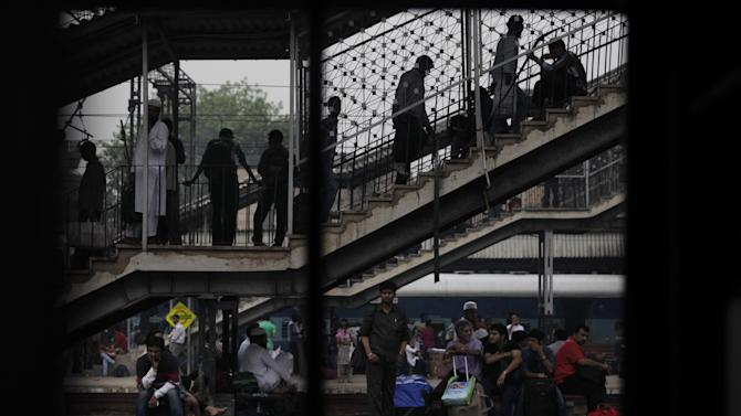 Stranded commuters wait for their trains to arrive at a train station in New Delhi, India, Monday, July 30, 2012. Northern India was plunged into darkness Monday after a supply grid tripped because of overloading, officials said. (AP Photo/Altaf Qadri)