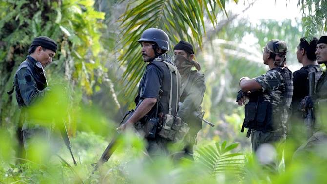 In this photo taken on March 2, 2013, a group of Malaysian police commandos stand guard near the area where the stand-off with Filipino gunmen took place in Tanduo village, Lahad Datu, Sabab, Malaysia. Malaysia is sending hundreds of soldiers to a Borneo state to help neutralize armed Filipino intruders who've killed 8 policemen in the country's bloodiest security emergency in years. Nineteen Filipino gunmen have been slain since Friday in skirmishes that shocked Malaysians unaccustomed to such violence in their country, which borders restive southern provinces in the Philippines and Thailand. (AP Photo/Bernama News Agency) MALAYSIA OUT, NO SALES, NO ARCHIVE