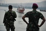 File photo shows Indonesian marines watching a rescue boat carrying asylum-seekers at Merak seaport in August. Asylum-seekers sent to Nauru will be forced initially to live in tents, Australia's Immigration Minister confirmed Tuesday