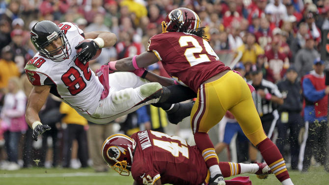 Atlanta Falcons tight end Tony Gonzalez is stopped short of the goal line by Washington Redskins strong safety DeJon Gomes (24) and free safety Madieu Williams (41) and during the first half of an NFL football game in Landover, Md., Sunday, Oct. 7, 2012. (AP Photo/Evan Vucci)