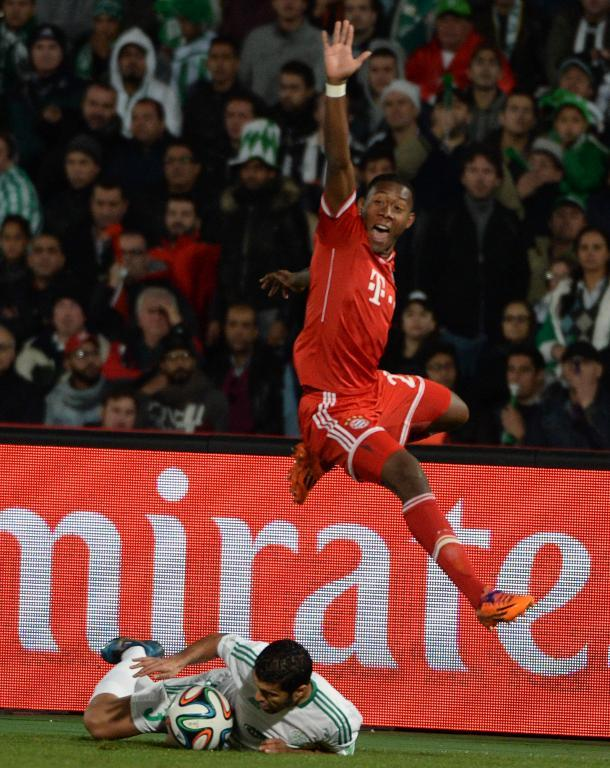 Bayern Munich's defender David Alaba calls for a hand ball call on Raja Casablanca's defender Zakaria El Hachimi (bottom) during their 2013 FIFA Club World Cup final match in the Moroccan city of Marrakesh, on December 21, 2013