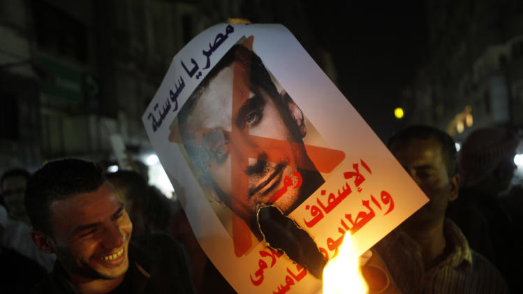 """In this Wednesday, Oct. 30, 2013 photo, Supporters of Defense Minister Gen. Abdel-Fattah el-Sissi burn a poster with a photo of Bassem Youssef, the man known as """"Egypt's Jon Stewart,"""" and Arabic that reads, """"not Egypt, you are degrading to the media, fifth column,"""" during a protest in Cairo, Egypt. Several complaints were filed against Youssef, after he mocked the pro-military fervor gripping Egypt in his first program of the season last week. Youssef also took jabs at the powerful El-Sissi, lionized in the local media after leading a July 3 overthrow that ousted the Islamist president. (AP Photo/Amr Nabil)"""