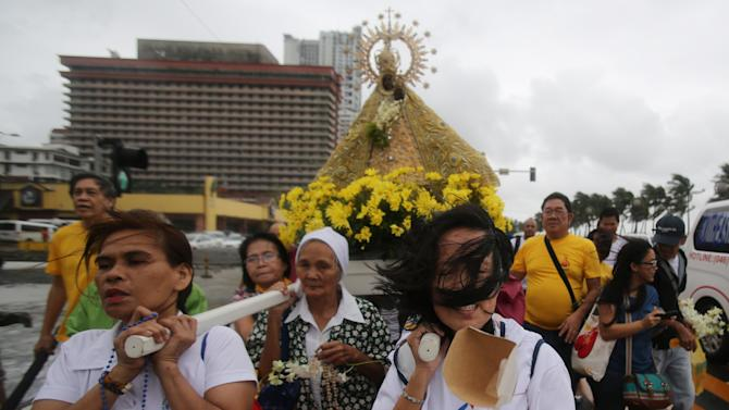 Filipino women devotees brave strong winds as they carry an image of the Lady of Penafrancia during a procession in Manila, Philippines on Sunday, Sept. 14, 2014. The Philippine weather bureau says Typhoon Kalmaegi, locally called Luis, was located based on all available data at 266 km North Northeast of Virac, Catanduanes or at 347 km East Southeast of Casiguran, Aurora with maximum winds of 120 kph and gustiness of up to 150 kph. It is forecast to move West Northwest at 20 kph. (AP Photo/Aaron Favila)