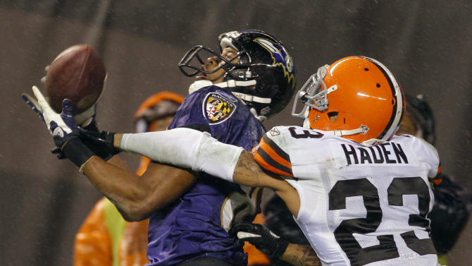 Baltimore Ravens wide receiver Lee Evans, left, cannot hold on to a pass under pressure by Cleveland Browns cornerback Joe Haden (23) in the fourth quarter of an NFL football game in the rain on Sunday, Dec. 4, 2011, in Cleveland. The Ravens won the game 24-10. (AP Photo/Amy Sancetta)