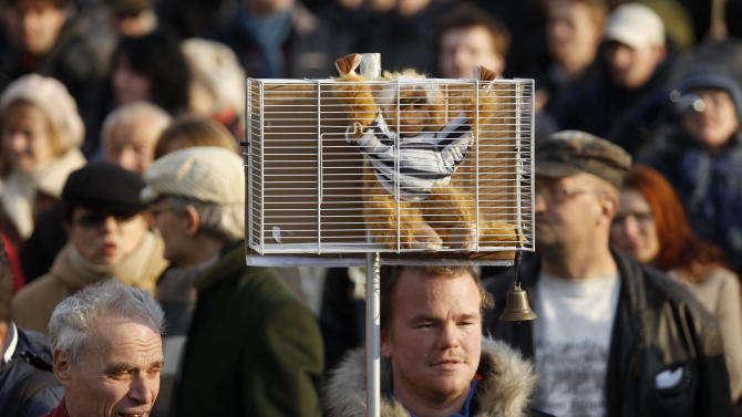 A protester holds a toy monkey in a cage during an anti corruption demonstration in Bratislava, Slovakia, Friday, March 9, 2012. Hundreds of Slovaks are protesting in the capital to demand that top politicians accused of corruption step down. Slovakia is holding early general elections on Saturday, March 10, 2012. (AP Photo/Petr David Josek)