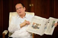 Philippine President Benigno Aquino shows a newspaper with a story about the resolution to a decades-long Muslim rebellion in the Philippines, at the Malacanang Palace in Manila. A final resolution to a decades-long Muslim rebellion in the Philippines is a long way off with many tough issues yet to be resolved, experts cautioned Monday, a day after a peace roadmap was unveiled