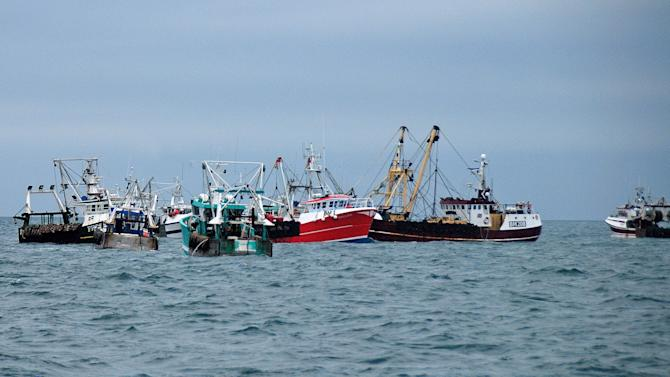 This Oct. 8, 2012 photo shows, British fish boats center and right,  being prevented to fish by French fishermen, in the English Channel, off Le Havre, western France. A bumper season for the French national dish of Coquilles St. Jacques has turned into a bitter dispute in the English Channel, as French fishermen angry over British expansion into their waters surrounded British boats in a show of maritime force.(AP Photo/Pierre Guillaume)