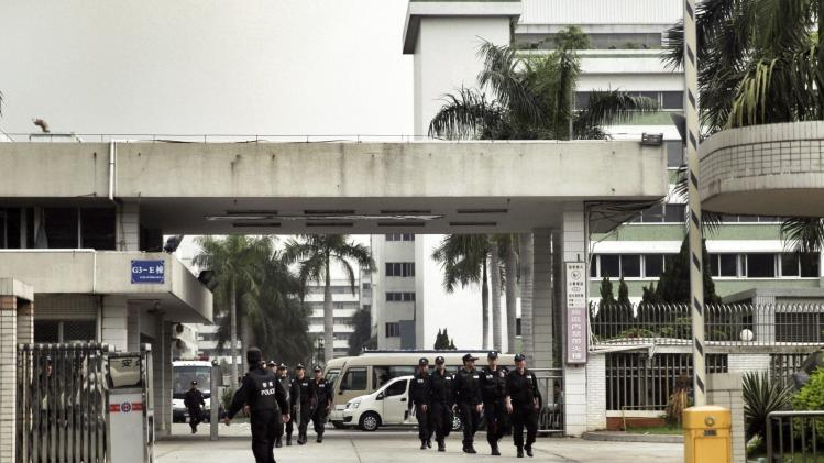 Police patrol as workers go on strike at the factory area of Yue Yuen Industrial, in Dongguan