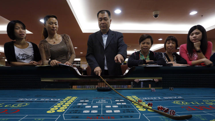 In this Nov. 25, 2012 photo, a gambling school students take a class in Macau, China. The students sitting around the roulette table are getting schooled on how to quickly calculate payoffs for the casino game by glancing at how the bets are placed. Elsewhere in the room, the biggest mock casino in Asia, other students are playing practice hands of blackjack or learning how to run a craps table. (AP Photo/Vincent Yu)