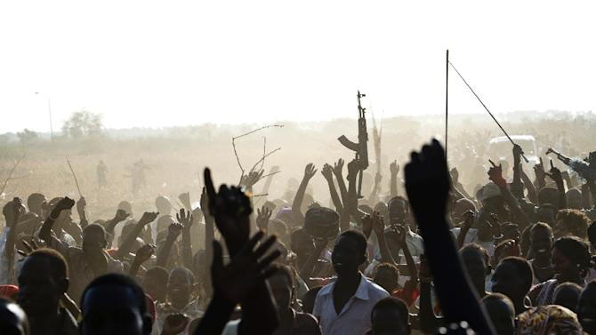 SPLA soldier waves his AK-47 as soldiers celebrate outside the United Nations Mission in the Republic of South Sudan base in Malakal after the SPLA claimed it had recaptured the town from rebels on March 19, 2014