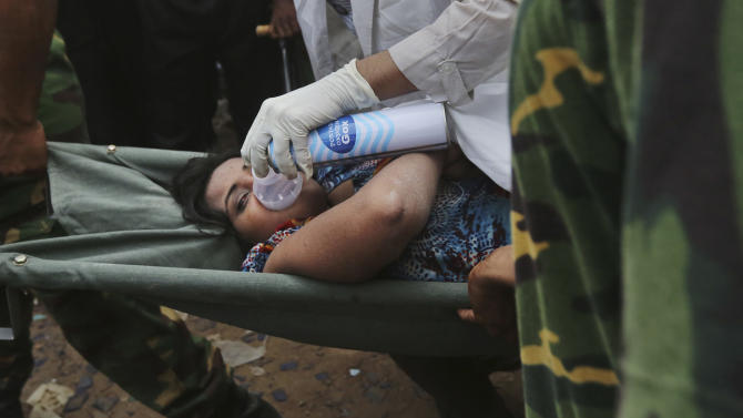 A Bangladeshi garment worker who was pulled alive from the rubble is wheeled on a stretcher at the site of a building that collapsed Wednesday in Savar, near Dhaka, Bangladesh, Friday, April 26, 2013. The death toll reached hundreds of people as rescuers continued to search for injured and missing, after a huge section of an eight-story building that housed several garment factories splintered into a pile of concrete.(AP Photo/Kevin Frayer)