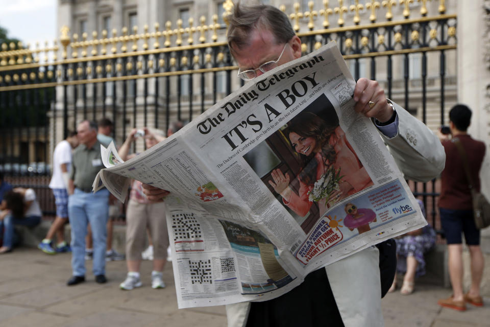 A man reads a newspaper carrying front page news of the birth of a baby boy of Prince William and Kate, Duchess of Cambridge, outside Buckingham Palace in London, Tuesday, July 23, 2013. (AP Photo/Sang Tan)