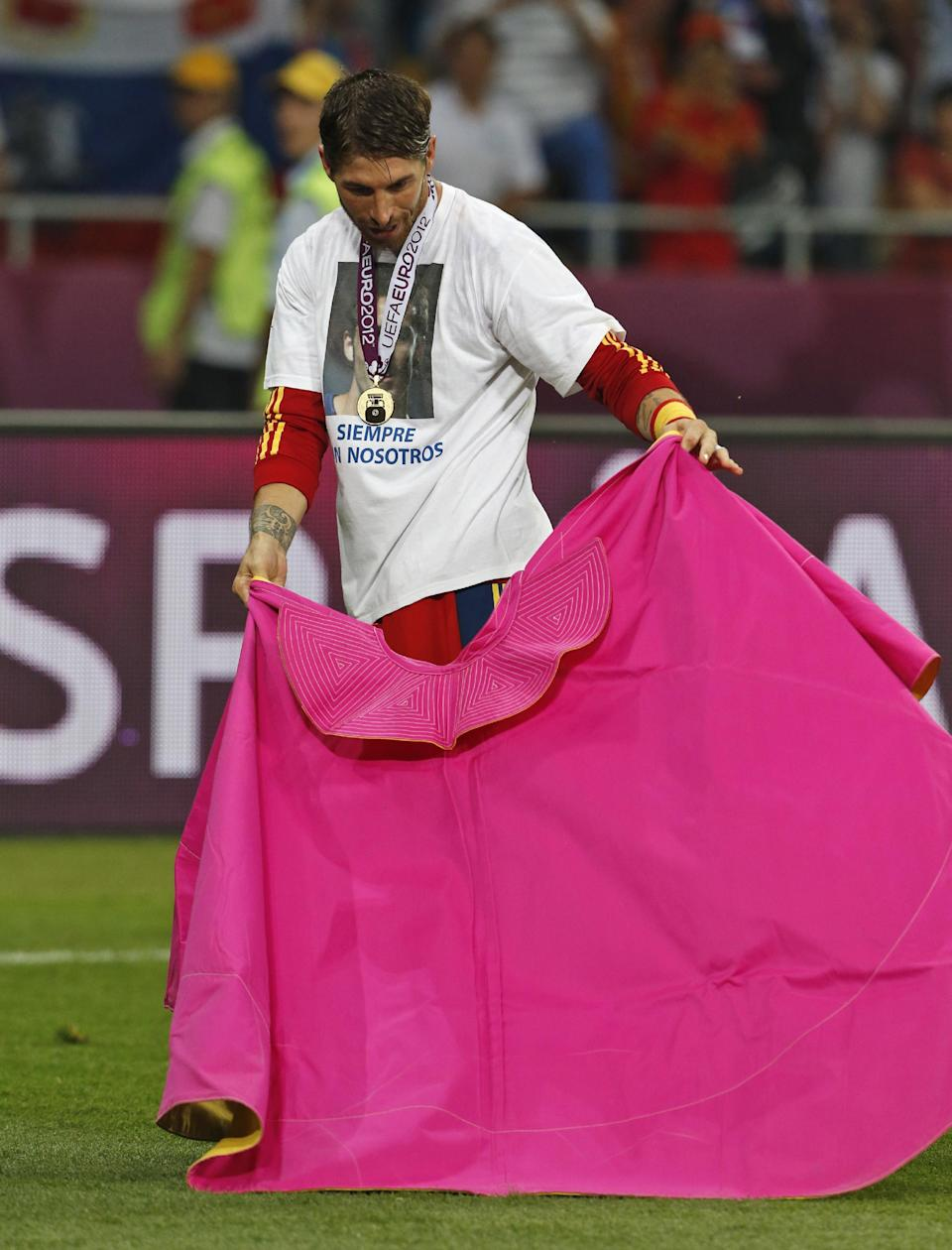 RESENDING WITH CORRECTED NAME- Spain's Sergio Ramos acts as a matador after the Euro 2012 soccer championship final  between Spain and Italy in Kiev, Ukraine, Monday, July 2, 2012. (AP Photo/Gregorio Borgia)