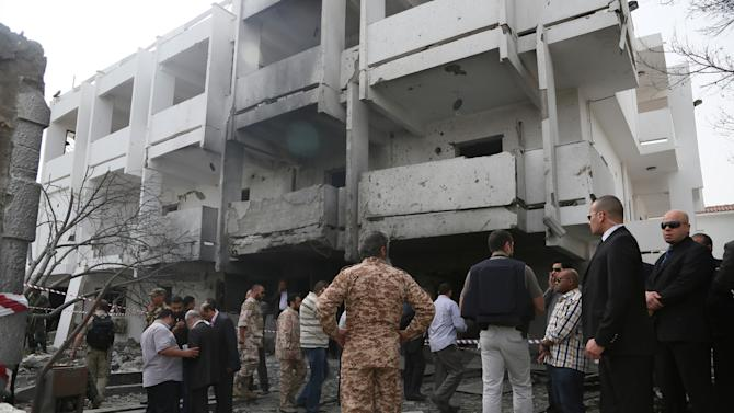 Security officers and officials inspect the site of a car bomb that targeted the French embassy wounding two French guards and causing extensive material damage in Tripoli, Libya, Tuesday, April 23, 2013. AN explosives-laden car was detonated just outside the embassy building in Tripoli's upscale al-Andalus neighborhood, officials said. (AP Photo/Abdul Majeed Forjani)
