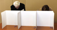 Croatia's president Ivo Josipovic, left, fills his ballot paper at a polling station in Zagreb, Croatia, Sunday, Jan. 22, 2012. Croatians vote Sunday in a nationwide referendum on whether to join the European Union, a test of how much the debt-stricken 27-nation bloc has lost its appeal among potential new members. (AP Photo/Darko Bandic)