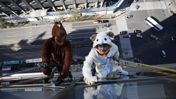 Window cleaners, dressed in horse and sheep costumes featuring animal signs from the Chinese zodiac calendar, work during an event in Tokyo