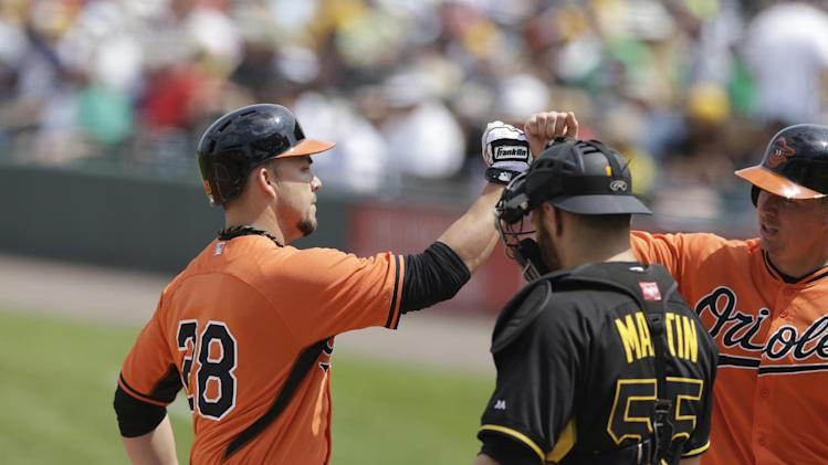 Baltimore Orioles' Steve Pearce, left, receives a high-five at the plate in front of Pittsburgh Pirates catcher Russell Martin, after hitting a two-run homerun during the fourth inning of a spring exhibition baseball game in Bradenton, Fla., Monday, March 10, 2014