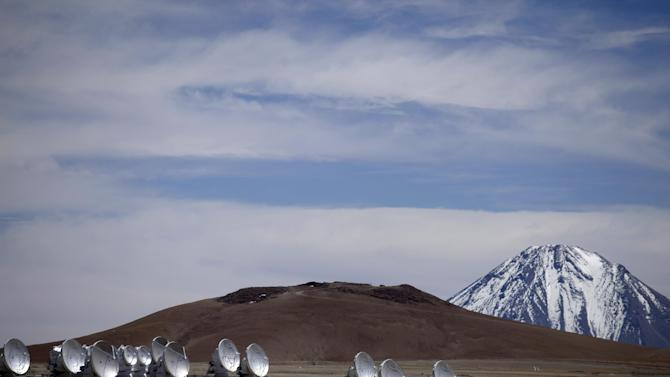 In this Sept. 27, 2012 photo, radio antennas face the sky as part of one of the worlds largest astronomy projects, the Atacama Large Millimeter/submillimeter Array (ALMA) in Chajnator in the Atacama desert in northern Chile. Linked as a single giant telescope, the radio antennas pick up wavelengths of light longer than anything visible to the human eye and colder than infrared telescopes, which are good at capturing images of distant suns but miss planets and clouds of gases from which stars are formed. (AP Photo/Jorge Saenz)