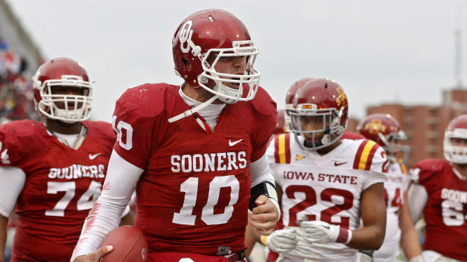 Iowa State safety Ter'Ran Benton (22) looks on as Oklahoma quarterback Blake Bell celebrates a touchdown in the second quarter of an NCAA college football game in Norman, Okla., Saturday, Nov. 26, 2011. (AP Photo/Sue Ogrocki)