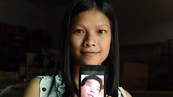 Vietnamese bride Vu Thi Hong Thuy poses with a photo of her Chinese husband in Weijian village, China's Henan province on July 30, 2014