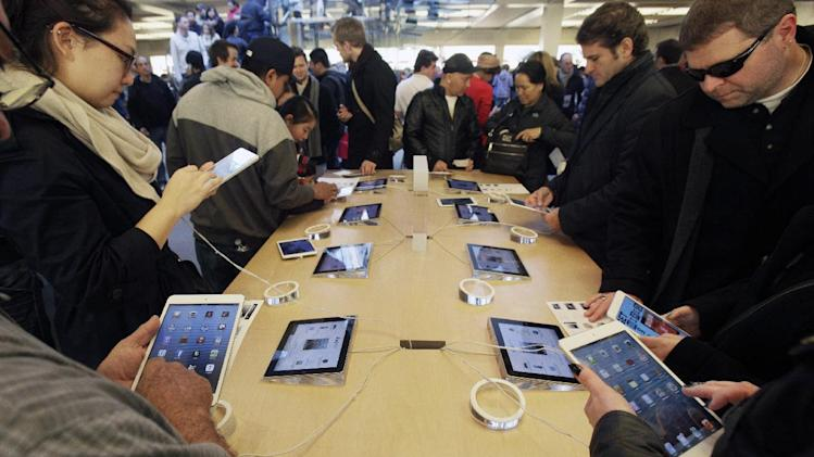 Shoppers at Apple's flagship store in New York, look at iPads and iPad Minis, Friday, Nov. 23, 2012.  Black Friday, the day when retailers traditionally turn a profit for the year, got a jump start this year as many stores opened just as families were finishing up Thanksgiving dinner. (AP Photo/Richard Drew)