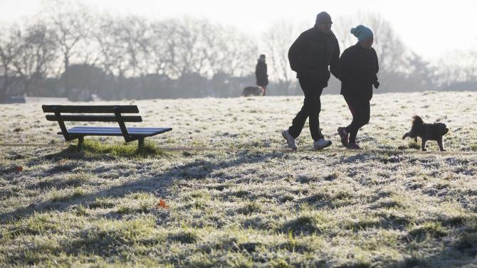 A couple run with a dog through a frost covered field in Hampstead Heath in north London