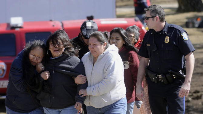 The family of Lyle Eagletail grieves after his body was recovered from the Big Sioux River below the falls at Falls Park in Sioux Falls, S.D. Saturday, March 16, 2013. Eagletail and 16-year-old Madison Wallace dove into the water on Thursday to rescue 6-year-old Garrett Wallace who did survive. Madison's body was recovered on Friday afternoon. (AP Photo/Argus Leader, Elisha Page)