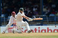Batsman Shane Watson (R) of Australia plays a shot as West Indies wicketkeeper Carlton Baugh (L) watches during the first day of the second-of-three Test matches between Australia and West Indies at Queen's Park Oval in Port of Spain, Trinidad