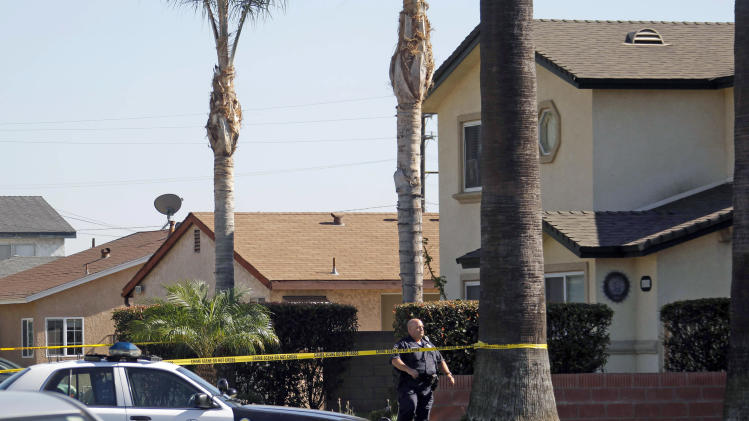 A police officer stands outside a two-story home, right, where one person was found shot to death in Downey, Calif., Wednesday, Oct. 24, 2012. Five people were shot and at least two died in shootings at a business and a residence in the Los Angeles suburb Wednesday, according to Downey police Lt. Dean Milligan.  The shootings occurred shortly after 11 a.m. at a business and at a nearby home, where family members of the business owner live. A woman was found dead at the home, he said. (AP Photo/Nick Ut)
