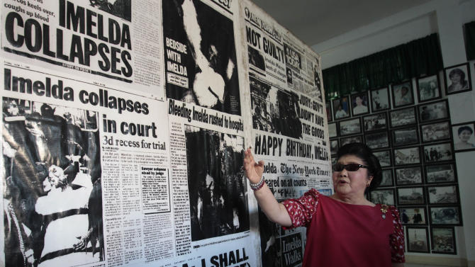 In this May 5, 2013 photo, former Philippine First Lady Imelda Marcos shows newspaper reports about her inside a gallery of the Marcoses in Batac, Ilocos Norte province, northern Philippines. Twenty-seven years after her dictator husband was ousted by a public revolt, Imelda Marcos has emerged as the Philippines' ultimate political survivor: She was back on the campaign trail this week, dazzling voters with her bouffant hairstyle, oversized jewelry and big talk in a bid to keep her seat in Congress. (AP Photo/Aaron Favila)