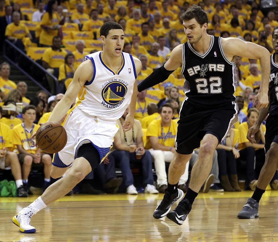 Golden State Warriors guard Klay Thompson (11) drives past San Antonio Spurs center Tiago Splitter (22) during the first quarter of Game 6 of a Western Conference semifinal NBA basketball playoff series in Oakland, Calif., Thursday, May 16, 2013. (AP Photo/Marcio Jose Sanchez)